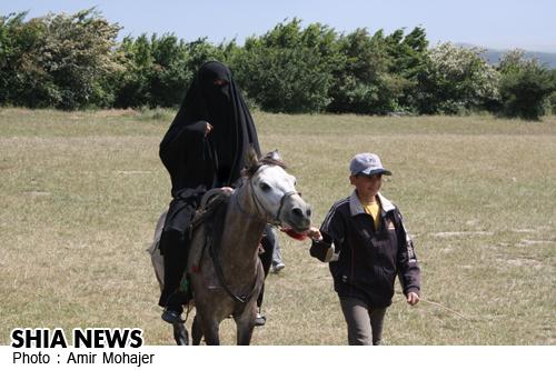 تصویری از یک بانوی محجبه در حال اسب سواری